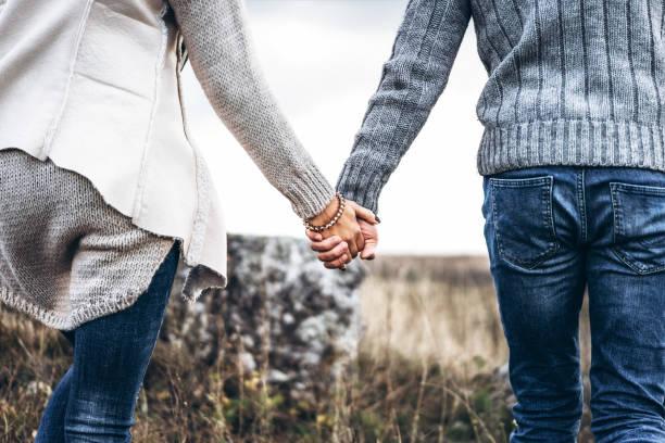 jolie jeune couple amoureux en plein air - se tenir par la main photos et images de collection