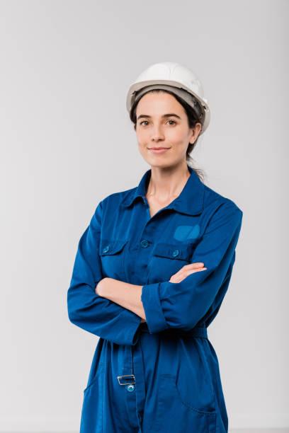 Bastante joven ingeniero femenino con armas cruzadas en ropa de trabajo azul y casco de seguridad - foto de stock