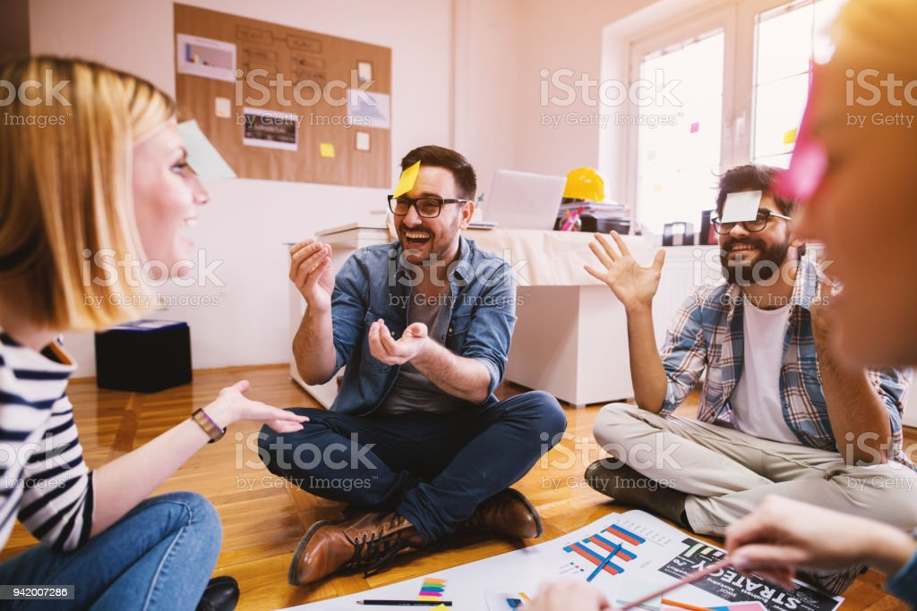 Pretty young designer coworkers enjoying free time and raising togetherness and team spirit while sitting in a circle on the floor of the office and playing games with paper stickers on the forehead. stock photo