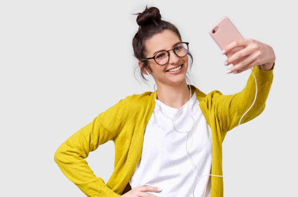 Pretty young European woman in casual clothes standing and taking a selfie isolated over white studio background. Pretty Caucasian brunette female wearing transparent spectacles making self portrait stock photo
