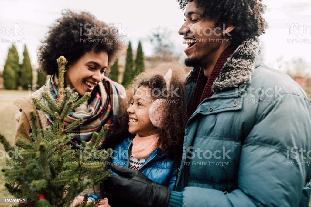 Pretty young family hugging while Christmas tree shopping