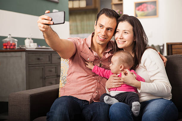 Pretty young family taking a selfie at home stock photo