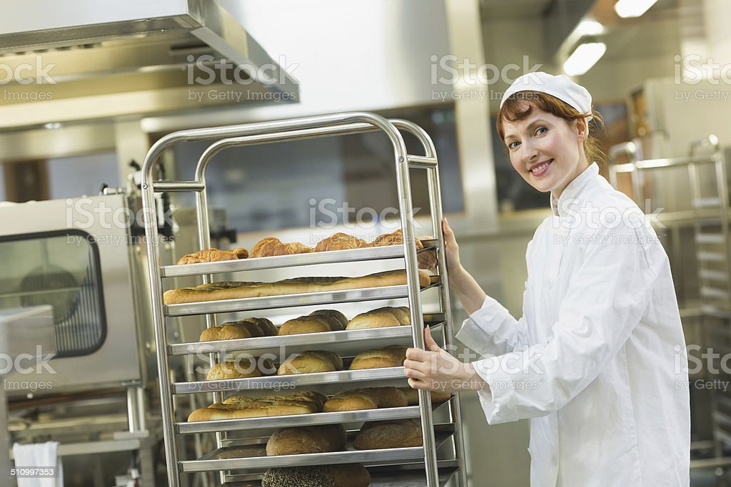 Pretty young female baker pushing a trolley stock photo