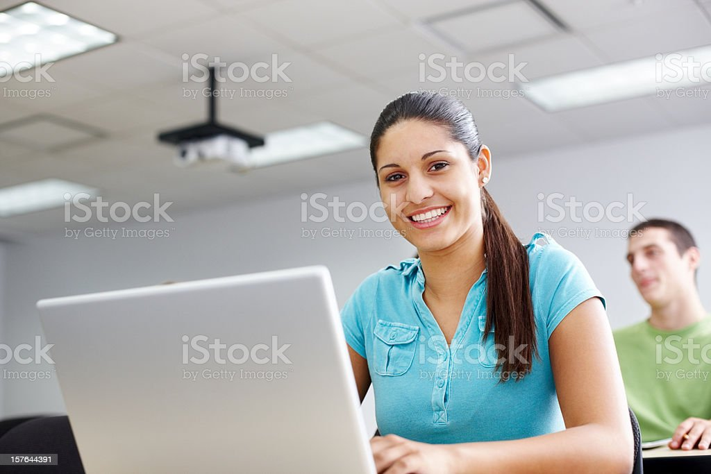 Pretty young female college student sitting in a classroom royalty-free stock photo