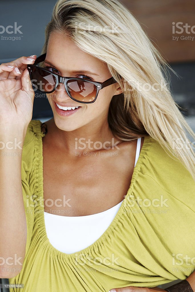 Pretty young female in sunglasses smiling confidently royalty-free stock photo
