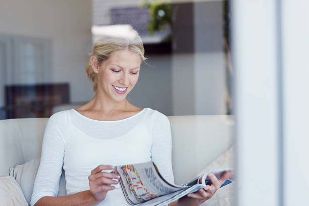 Pretty young female reading a magazine at home stock photo