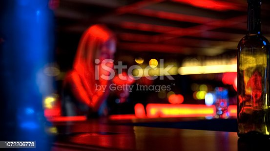 istock Pretty young female with glass drinking cocktail at bar, blurred background 1072206778