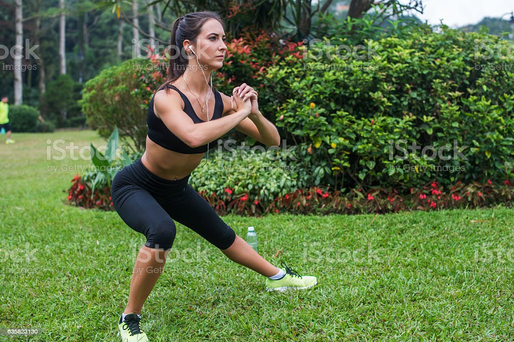 Pretty young fit woman doing stretching exercises in park. Fitness stock photo