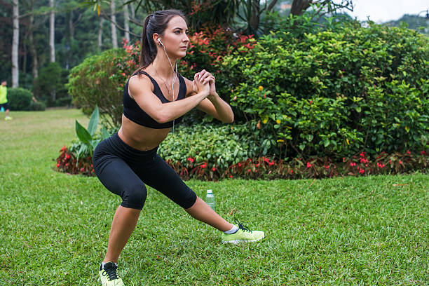 pretty young fit woman doing stretching exercises in park. fitness - lunge stock photos and pictures