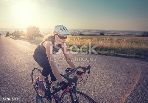 Pretty Young Fit Woman Riding Bike Up the Hill at Sunset