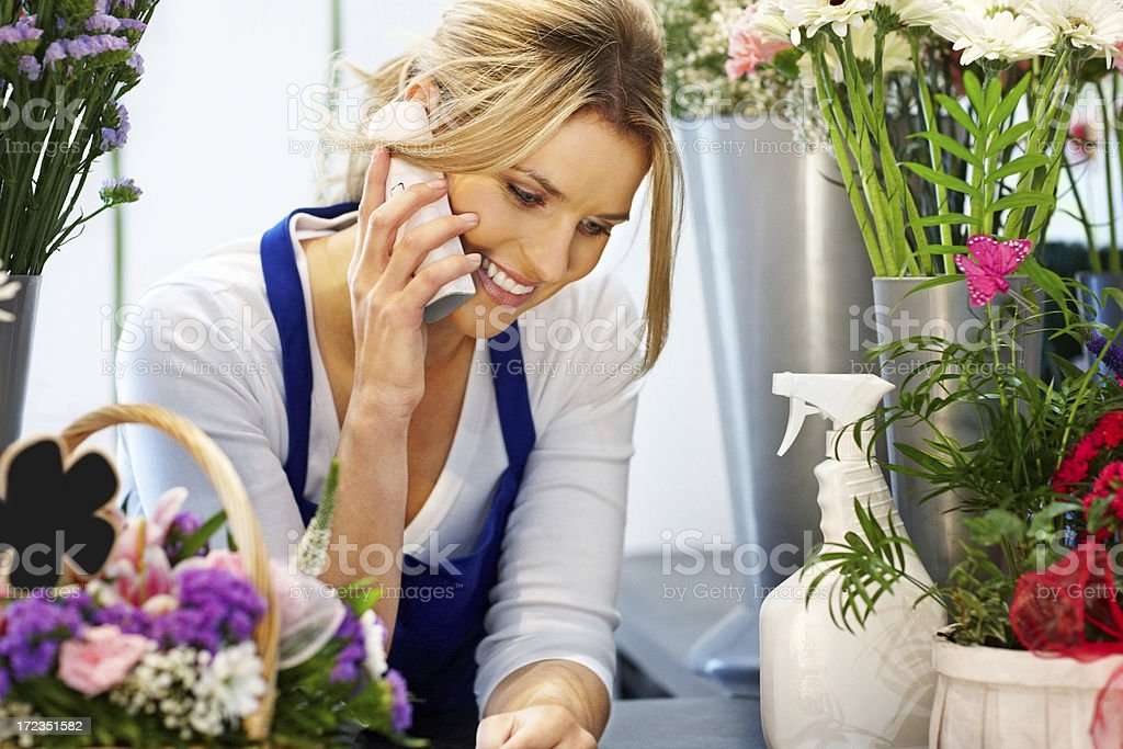 Pretty young florist talking on phone royalty-free stock photo