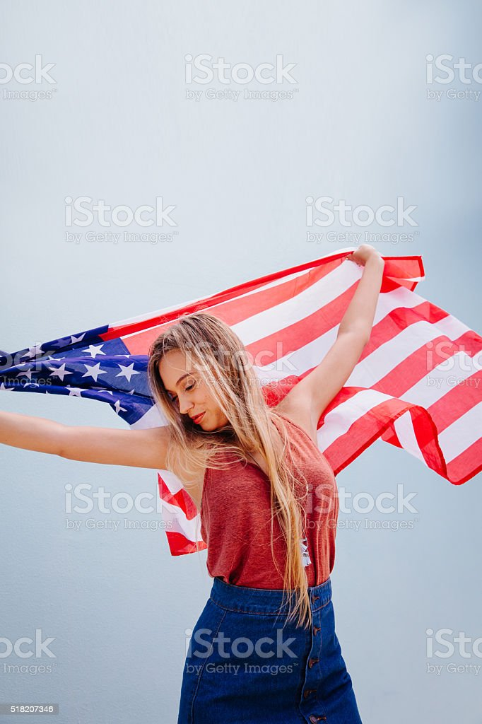 Pretty young funny American patriotic girl dancing stock photo