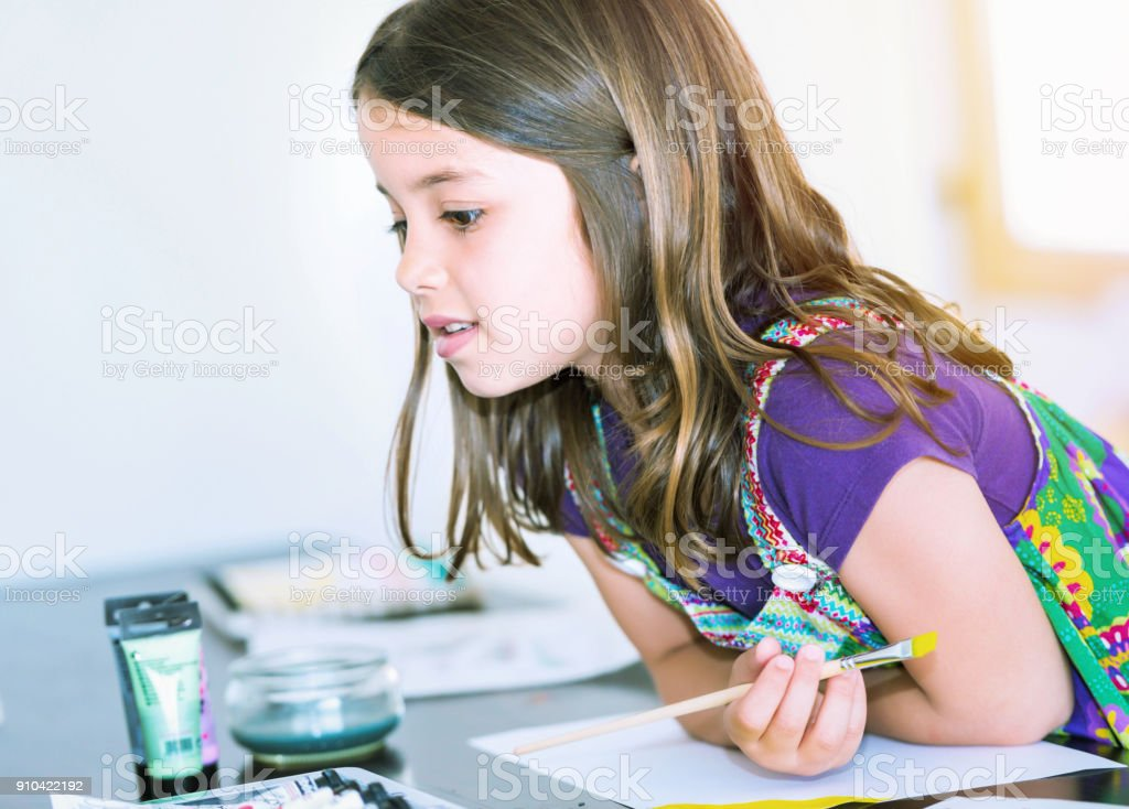pretty young girl doing paint with her stock photo