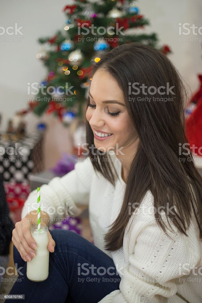Pretty young girl dreaming of Christmas, sparkling Christmas tree behind zbiór zdjęć royalty-free