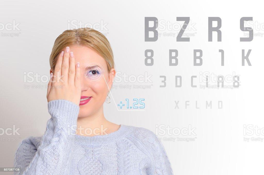 Pretty young girl examining her eyesight stock photo