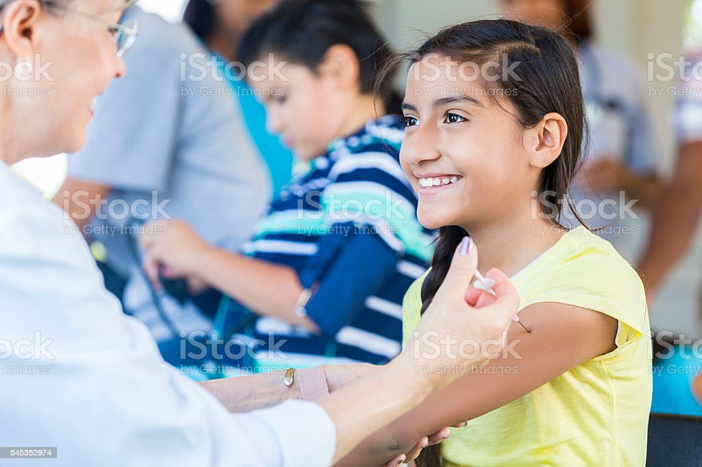 Pretty young girl getting her flu shot at free clinic stock photo