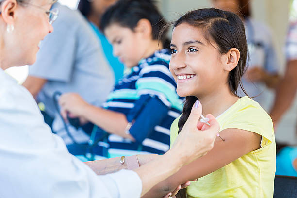 Pretty young girl getting her flu shot at free clinic Pretty young hispanic girl getting a flu short from a senior caucasian doctor. The young girl is smiling up at her doctor. She is wearing a yellow t-shirt. There are other children and people behind her. tetanus stock pictures, royalty-free photos & images