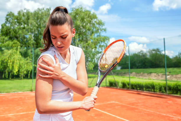 Pretty young girl injured during tennis practice stock photo