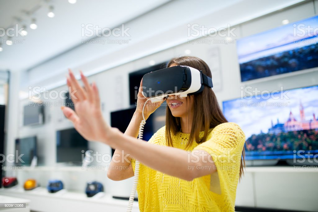 Pretty young girl is testing VR headset in the electronics store. stock photo