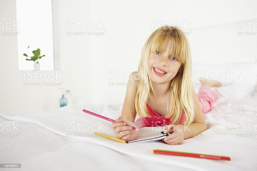 Pretty young girl lying on bed stock photo