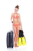 Full length image of pretty young girl in bikini with fins and luggage on white background