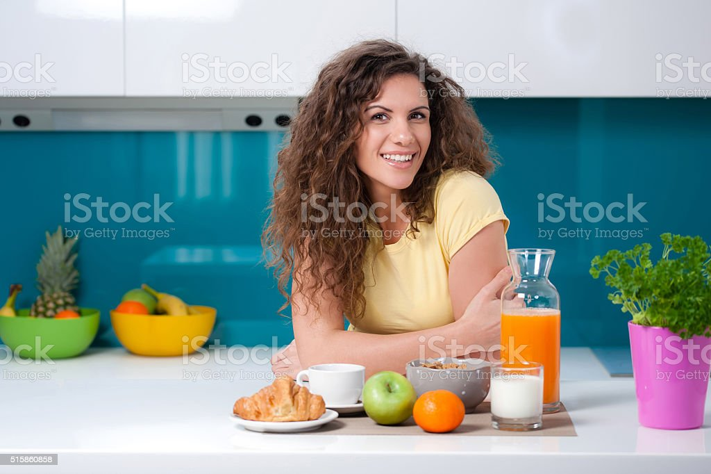 Pretty young girl sitting at the kitchen table, having breakfast. stock photo