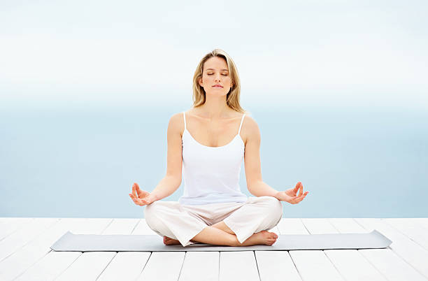 Pretty young girl sitting in lotus position on a dock  lotus position stock pictures, royalty-free photos & images