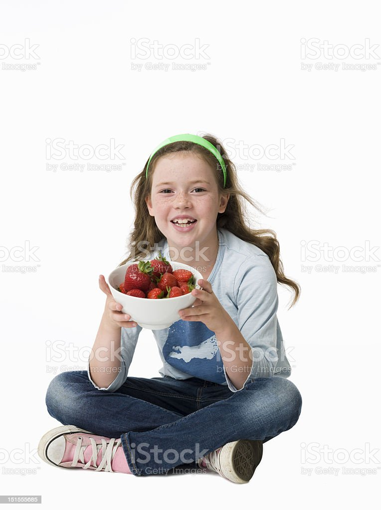 Pretty, young girl sitting on floor holding bowl of strawberries stock photo