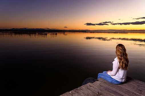 Pretty young girl sitting on the edge of a jetty of a lake at sunset in Valencia.