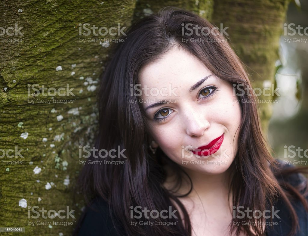 Pretty Young Girl Smiling in Front of a Tree stock photo