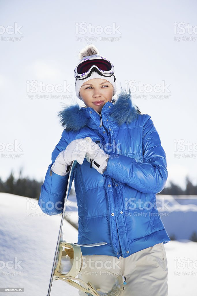 Pretty young girl standing with snowboard in her hand stock photo