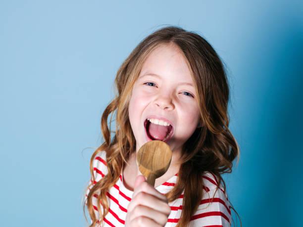 hübsches junges Mädchen benutzt Kochlöffel als Mikrofon und singt vor blauem Hintergrund – Foto