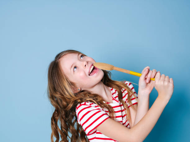 pretty young girl uses cooking spoon as microphone and sings in front of blue background stock photo