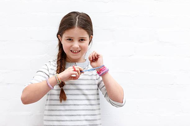 hübsche junge mädchen tragen farbenfrohe webstuhl-band - armband i gummi stock-fotos und bilder