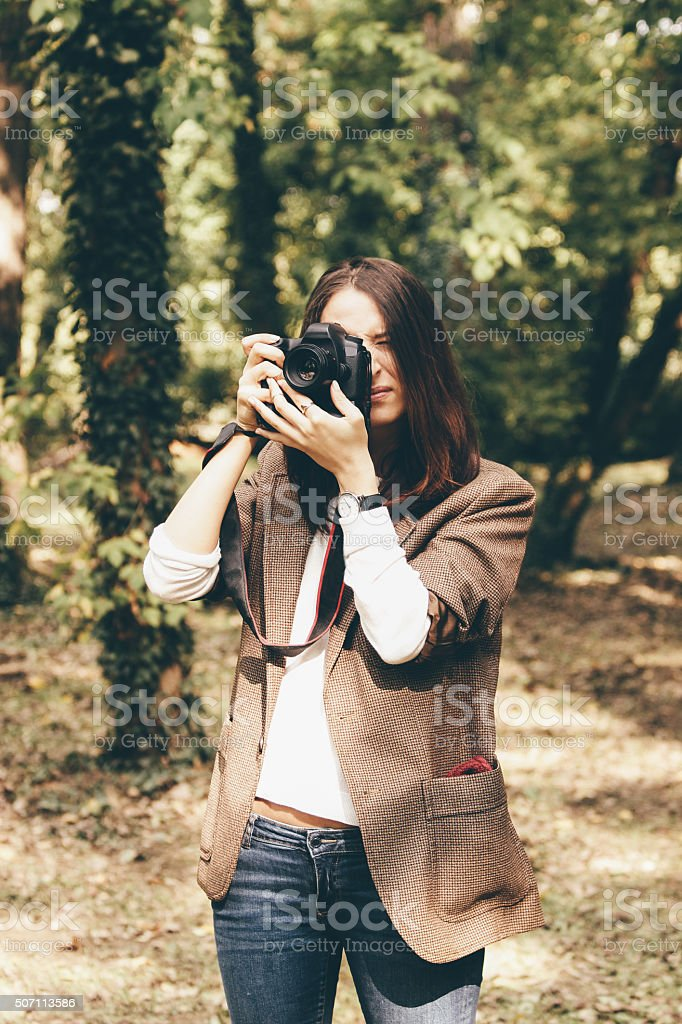 Pretty young girl with camera taking photos in the forest stock photo