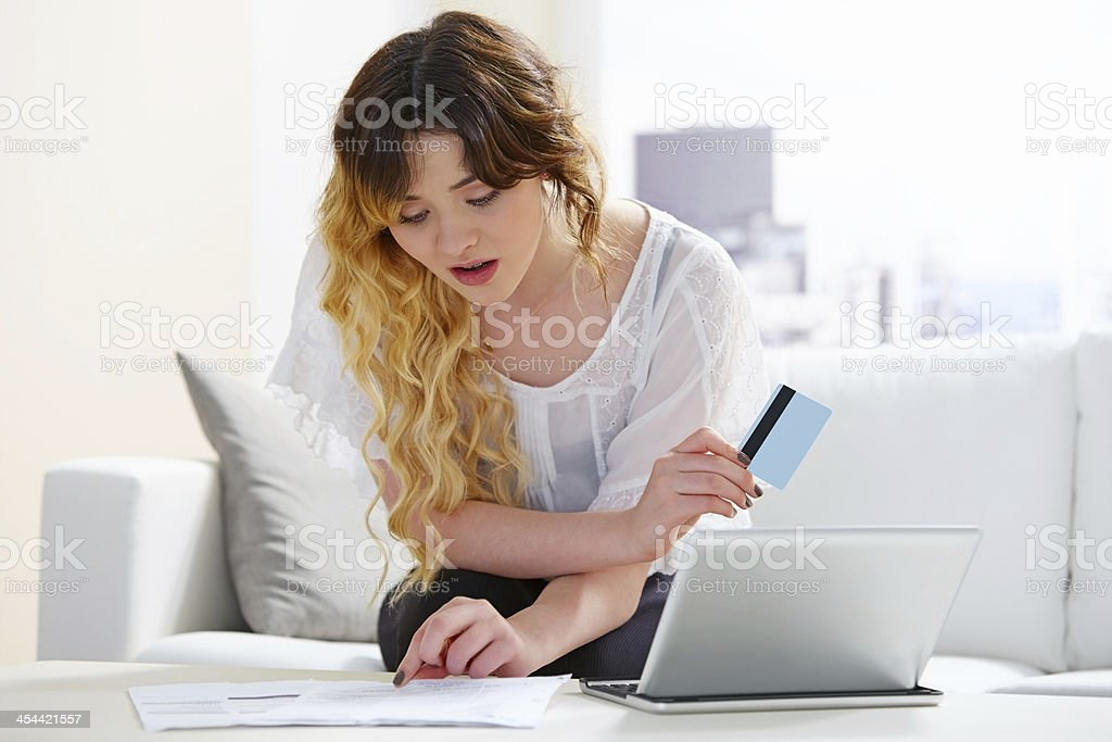Pretty young girl with laptop checking her credit card bills royalty-free stock photo