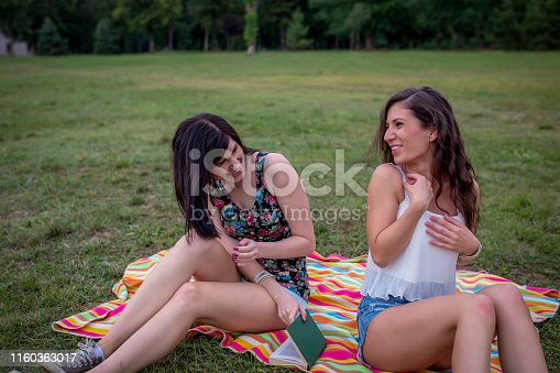 Pretty young girls smiling with pleasure as she listens to music with her eyes closed in bliss while lying on the grass in a green lush garden enjoying the spring sunshine