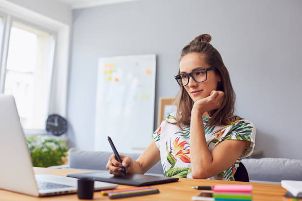 Pretty young graphic designer working in her home office Pretty young graphic designer working in her home office illustrator stock pictures, royalty-free photos & images
