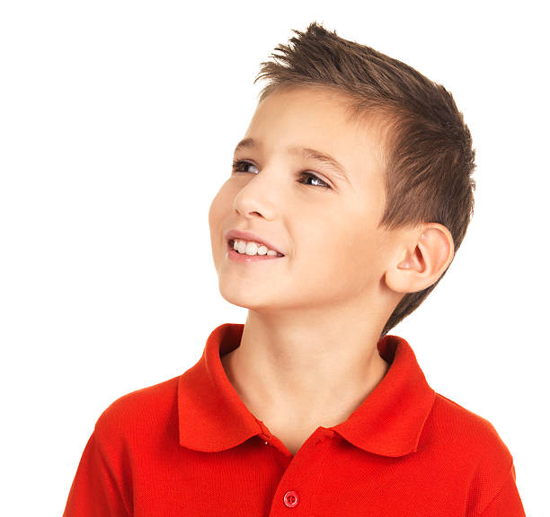 Pretty young happy boy looking away stock photo