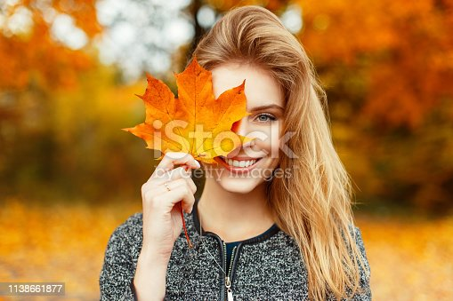 istock Pretty young happy young woman in stylish clothes with a beautiful smile holds in her hand an autumn gold-yellow leaf near face on a warm autumn day in the park. Funny happy girl enjoys weekend. 1138661877