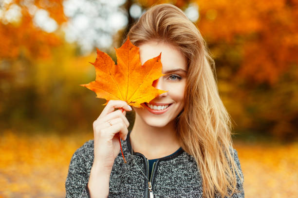 pretty young happy young woman in stylish clothes with a beautiful smile holds in her hand an autumn gold-yellow leaf near face on a warm autumn day in the park. funny happy girl enjoys weekend. - woman portrait forest foto e immagini stock