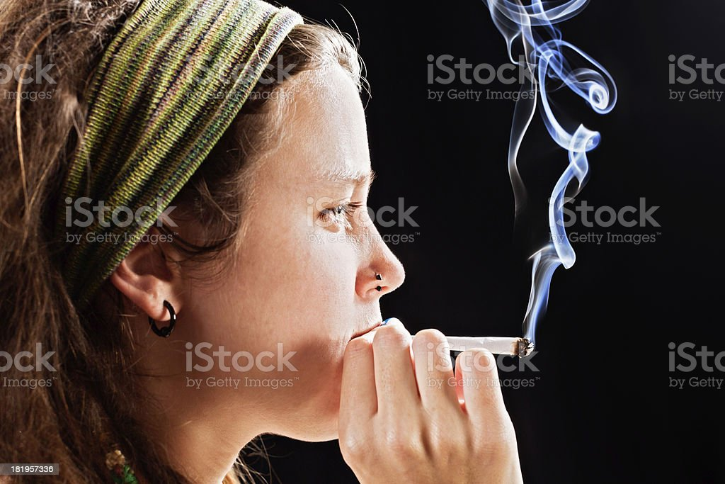 Pretty young hippie takes a toke of marjiuana stock photo