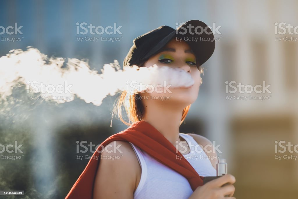 Pretty young hipster asian woman in black hat vape ecig, vaping device at the sunset. Toned image. Closeup Pretty young asian girl vape popular ecig gadget,vaping device.Happy brunette vaper girl with e-cig.Portrait of smoker female model with electronic cigarette vaporizer.Ejuice vaping with fruit flavor liquid 25-29 Years Stock Photo