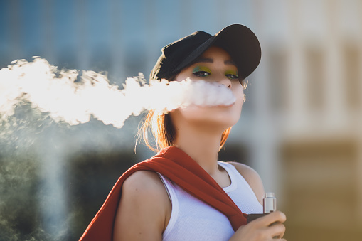Pretty Young Hipster Asian Woman In Black Hat Vape Ecig Vaping Device At The Sunset Toned Image Closeup Stock Photo - Download Image Now