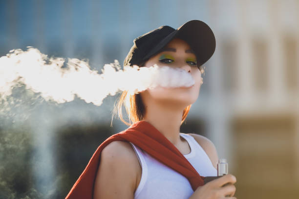 Pretty young hipster asian woman in black hat vape ecig, vaping device at the sunset. Toned image. Closeup Pretty young asian girl vape popular ecig gadget,vaping device.Happy brunette vaper girl with e-cig.Portrait of smoker female model with electronic cigarette vaporizer.Ejuice vaping with fruit flavor liquid electronic cigarette stock pictures, royalty-free photos & images