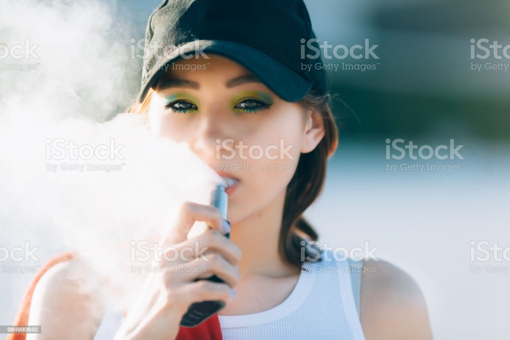 Pretty young hipster asian woman in black hat vape ecig, vaping device at the sunset. Toned image. Closeup stock photo