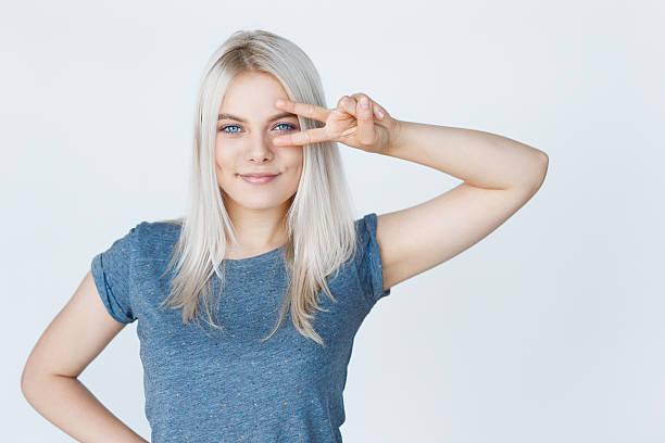 pretty young hipster teenage girl gesturing peace - capelli ossigenati foto e immagini stock