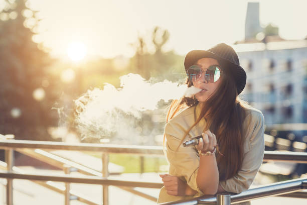 Pretty young hipster woman in black hat vape ecig, vaping device at the sunset. Toned image Pretty young girl vape popular ecig gadget,vaping device.Happy brunette vaper girl with e-cig.Portrait of smoker female model with electronic cigarette vaporizer.Ejuice vaping with fruit flavor liquid electronic cigarette stock pictures, royalty-free photos & images