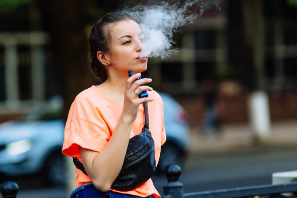 꽤 젊은 hipster 여자 vape ecig, 석양에 vaping 장치 몸매 이미지 - 전자담배 뉴스 사진 이미지