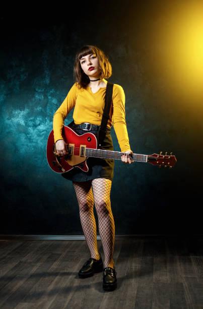 hübsche junge hipster-frau mit lockigen haaren mit roter gitarre in neonlicht. rockmusiker spielt elektrische gitarre. 90er-jahre-konzept. - bands der 90er stock-fotos und bilder